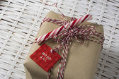 Gift box, tied with red and white cord, and candy can — Stock Photo