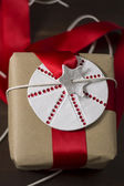 Gift rustic, with red ribbon and star label — Stock Photo