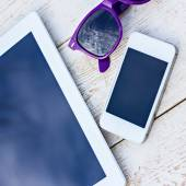 Tablet computer, mobile phone and sunglasses on a wooden table — Stock Photo