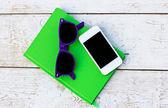 Notebook, cellulare e occhiali da sole su un tavolo in legno — Foto Stock