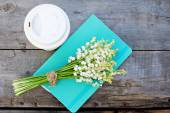 Diary, a glass of coffee and  lilies of valley  on the table — Стоковое фото