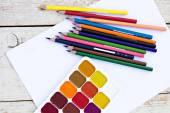 Цветные карандаши, акварель и бумаги на столе. Художник на рабочем месте. — Стоковое фото