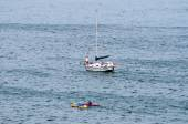 Sailboat and canoes in the sea near Gordons Bay — Stock Photo