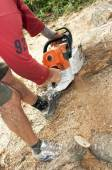 Gasoline powered  chainsaw on pile of cut wood — Stock Photo