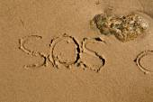 SOS written in sand — Stock Photo
