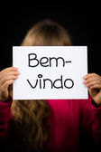Child holding sign with Portuguese word Bem-vindo - Welcome — Stock Photo