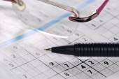 Pencil and glasses lying on a newspaper with a sudoku puzzle — Stock Photo