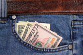 Several dollars banknotes seen from the pocket of jeans — Stock Photo