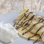 Crepe with banana and chocolate sauce — Stock Photo #66079643