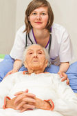 Young nurse caregiving an old lady lying in bed — Stock Photo