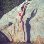 Outdoor portrait young woman doing exercise yoga coast of sea on wild rocky seashore beach stone rock — Stock Photo #52339205