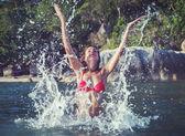 Beautiful young woman bikini splashing water having fun playing in sea on beach vintage retro style toned color — Stock Photo