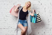 Adorable blond girl against the wall with shopping bags new purchases laughing out loud wearing summer clothes — Stock Photo
