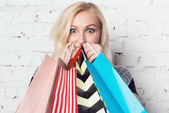 Gorgeous girl  absolutely happy with new purchases and hiding behind them. Amazing blue eyes peeping out of shopping bags. — Stock Photo