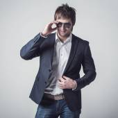 Fashion portrait of the young beautiful man posing in sun glasses over gray background — Stock Photo
