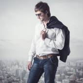 Confident, ambitious good looking man on the top of city with a jacker his shoulder. — Stock Photo