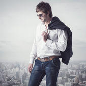 Confident, ambitious good looking man on the top of city with a jacker his shoulder. — Foto de Stock