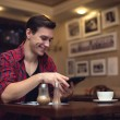 Young smiling attractive man uses his tablet in the lunchtime at cafe — Stock Photo #65387843
