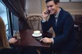 Handsome entrepreneur enjoying his launch in a cafe talking with someone by the phone. — Stock Photo