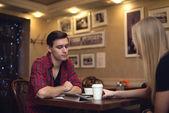 Dois amigos hipster homem jovem estão sentados na frente do outro, o café e bate-papo com uma xícara de café — Fotografia Stock