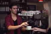 Hipster barista in  plaid shirt adds cinnamon customers cofee. — Stock Photo