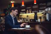 Young attractive businessman in a suit drinking coffee and using tablet to read news — Stock Photo