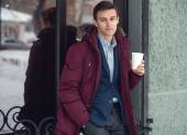 Young man in winter coat woth coffee to go standing against the cafe wall — Stock Photo