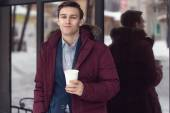 Young businessman in winter coat takes coffee to go a cafe. — Stock fotografie