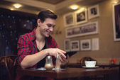 Young smiling attractive man uses his tablet in the lunchtime at cafe — Stockfoto