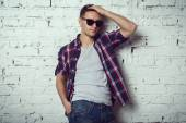 Casual handsome attractive hipster guy man with sunglasses his hand in the hair. — Stock Photo