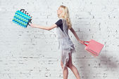 Amazing blond girl is going shopping with couple of colorful bags in her hands. — Stock Photo