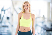 Fitness fit young blond woman standing against sport gym — Stok fotoğraf