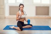 Beautiful athletic sporty woman sitting on yoga mat after some exercises with blue shaker in her hand  and white towel. — Stock Photo