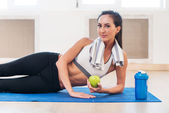 Caucasian beautiful healthy athletic sportive girl with green apple and Yoga Mat shaker. — Stock Photo
