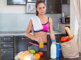 Pretty attractive athletic sportive lady woman standing in kitchen with a towel on her shoulder and healthy food fresh fruits milk bread around drinking cold drink beverage — Stockfoto