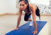 Young athletic sporty slim woman doing exercises on the blue mat looking straight forward. — Stock Photo