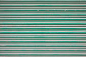 Large green metallic tin stripy fence background with scratches — Stock Photo