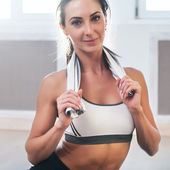 Pretty athletic sporty girls is smiling holding a towel after the training and looking at camera. — Stock Photo
