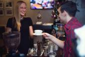Pretty blond girl taking her order with pleasant smile. Barista is passing cup pf cofee — Stockfoto