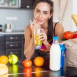 Pretty attractive athletic active sportive lady woman standing in kitchen and healthy food fresh fruits milk bread around holding glass with juice — Stock Photo #69278775