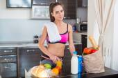 Pretty attractive athletic active sportive lady woman standing in kitchen with a towel on her shoulder and healthy food fresh fruits milk bread — Stockfoto