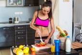 Pretty attractive athletic active sportive lady woman standing in kitchen with a towel on her shoulder and healthy food fresh fruits milk bread — Stock Photo