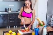 Athletic active sportive woman standing in kitchen with a knife her hand prepares healthy food fresh fruits milk bread on table — Foto de Stock
