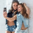 Girls friends taking selfie picture. Two beautiful young women having fun making photo and grimacing with mobile phone — Foto de Stock   #70301677