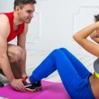 Man helping a woman or girl in making abdominal crunch, exercises concept training exercising workout fitness aerobic — Stock Photo #70479659