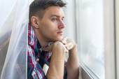 Handsome pensive man guy watching through the window concept sadness sorrow pain waiting — Stok fotoğraf