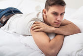 Handsome man guy in white T-shirt and blue jeans lying on a bed. — Stock Photo