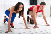 Beautiful girl and handsome guy in strat position for a run on the white wooden floor sports hall — Stock Photo