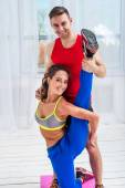 Young woman doing streching exercises with man smiling looking at camera concept training exercising workout fitness aerobic — Stock Photo