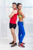 Athletic sporty couple friends woman and man trainers or coach client in sport hall gym standing arms crossed sportsmen professionals looking at camera — Stock Photo